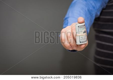 A man holding some one hundred dollar bills rolled up in his hand