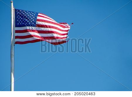 American flag flying on pole with frayed edge