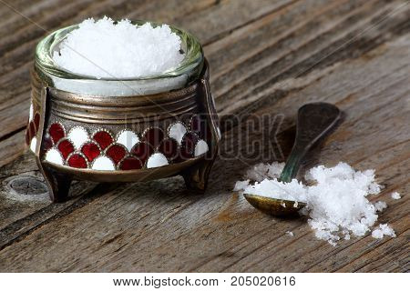 Nutritional salt in an old salt cellar on a gray wooden table