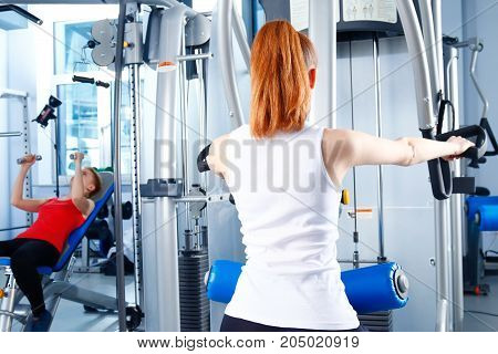 Beautiful girl at the gym exercising on trainers. Beautiful girl.