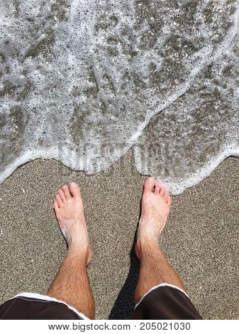 Man legs and feet by the ocean.