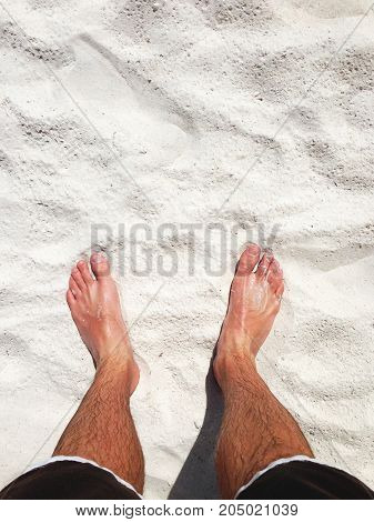 a man's legs and feet in white sand.