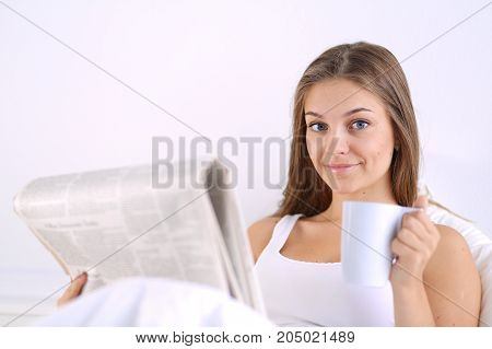 A pretty young woman reading the newspaper in bed and enjoying a cup of tea