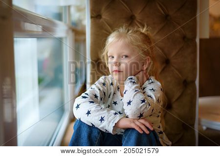young blonde girl posing by the window in a cafe