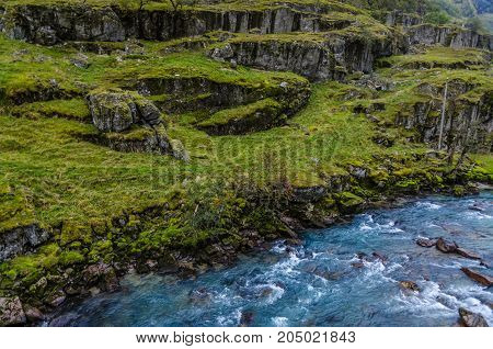 View of the mountain river ind green shore. Norway.