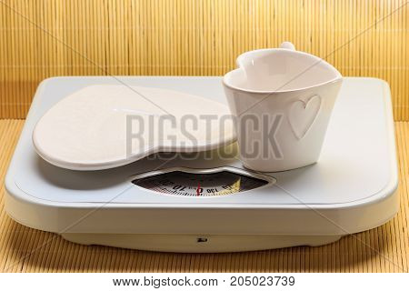 Empty Plate Saucer And Mug Cup On Weighing Scale.
