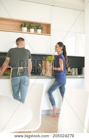 Beautiful young couple is having fun in kitchen at home