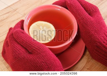 Hand Of Woman In Woolen Gloves Holding Cup Of Hot Tea On Wooden Table