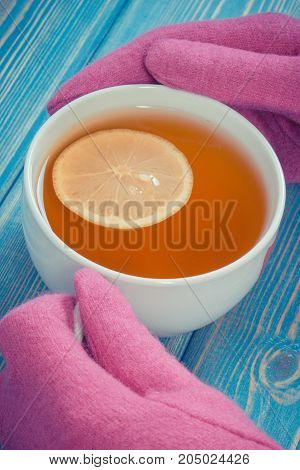 Vintage Photo, Hand Of Woman In Woolen Gloves Holding Cup Of Tea On Table