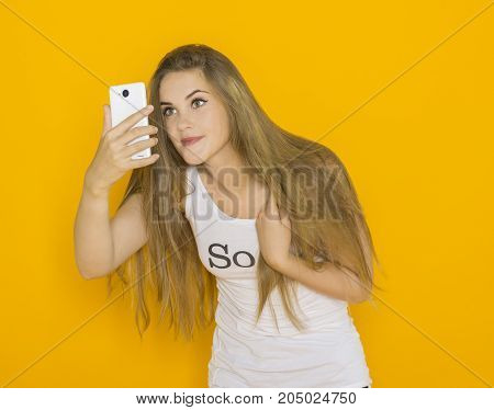 Unhappy young attractive woman with tousled hair very surprised something on her smartphone. Funny girl with mobile phone reads message. Studio shot orange background