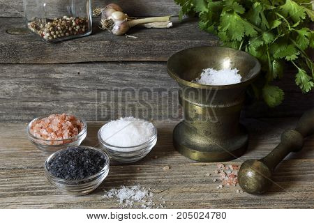 Salt of different types - sea, black, himalayan on a kitchen wooden table