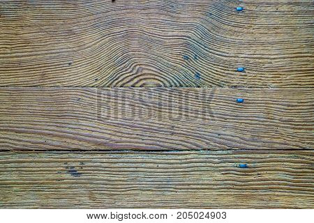 old wooden floor from boards fastened with metal nails with rectangular heads background
