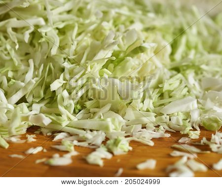pieces of chopped cabbage are on a wooden surface