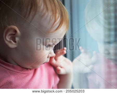 Small child looks out of the window of his house