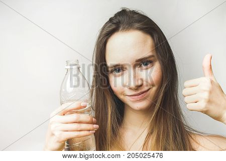 Surprised fitness woman with bottle of water shows like with thumb