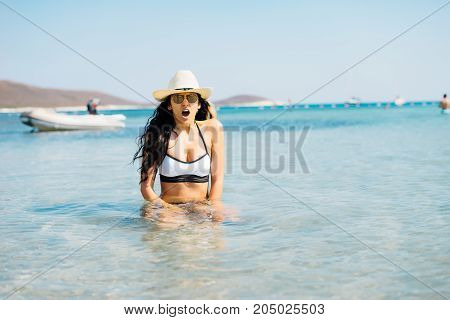 A surprised young woman in a hat bathes in cold water and cries out