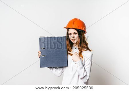 Young female construction worker in helmet holding a folder and pointing at it