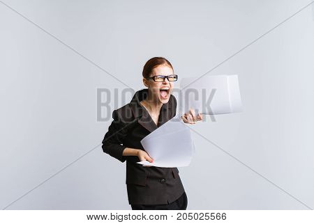 An angry upset businesswoman in a suit is screaming and angry, a tired office worker in stress, papers