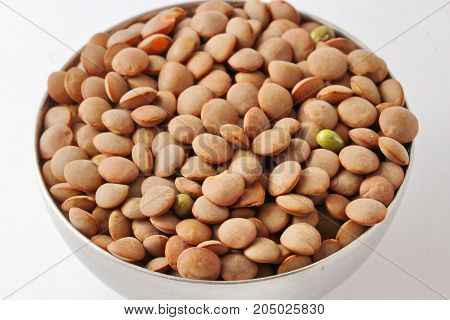 Close up of uncooked brown lentils in a bowl