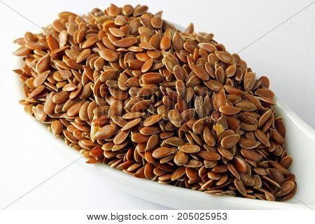 Flax seeds in a white spoon isolated on white background.