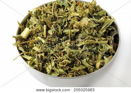 A close up of dried kasoori methi or dried fenugreek leaves in a steel bowl isolated on white background.