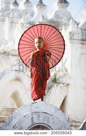 Novices under umbrellas at historic temple Mingun Mandalay Myanmar