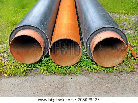 Three steel pipes lie on a grass. Two of them with isolation. Pipes will be used for construction or reconstruction of a heat conductor. Background.