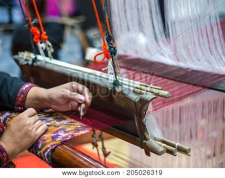 Thai artist demonstrates to make handicraft cloth with local apparatus