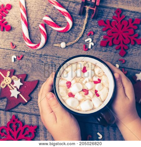 Woman Girl Holding Hot Chocolate Cup. Christmas Holiday Card With Red Decoration. New Year Theme. Christmas Tradition Drink on Wooden Background Table. Copy Space Top view