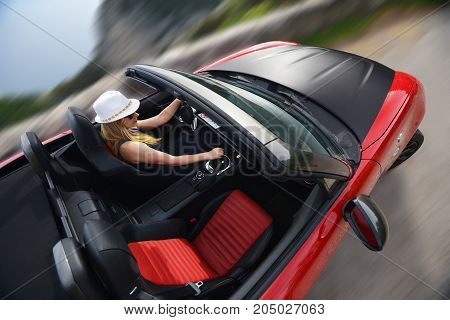 Woman and red cabriolet on winding mountain road