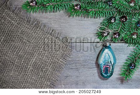 Christmas and new year background. Branch of green fir with a toy house on wooden surface and cloth vintage