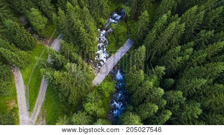 Road among wooded mountains frop top view