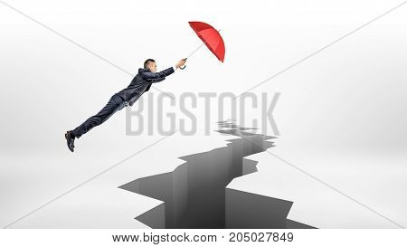 A businessman uses a large red umbrella to fly over a long earthquake crack on white background. Business insurance. Corporate support. Troubles and solutions.