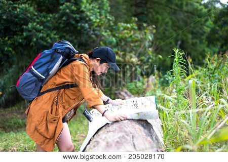Asia woman hiker or traveler with backpack checks map to find directions in wilderness area real explorer. Travel Concept.