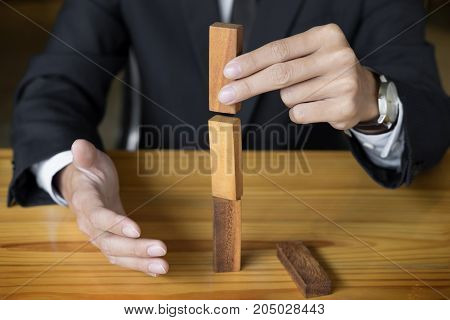 Planning risk and wealth strategy in business concept businessman and insurance gambling placing wooden block on a tower.