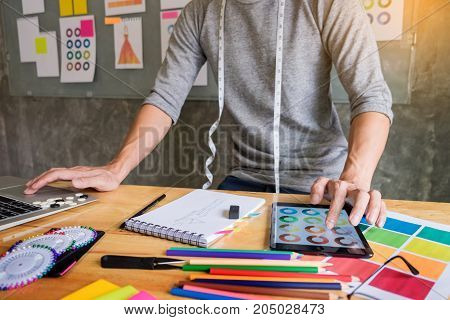 men working as fashion designer choosing on colour chart for clothes in digital tablet at workplace studio