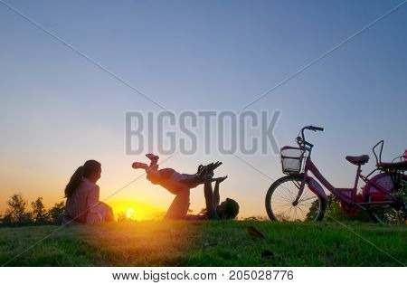 Father raising kids up in the air sky in sunset holiday at Chatuchak Park Bangkok City Thailand. Family concept