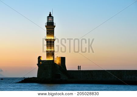 Lighthouse silhouette at sunset in Chania Crete Greece.