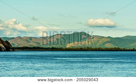 Pacific Ocean With Morning Cloudy Sky And Colorful Mountains.