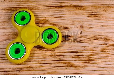 Yellow Fidget Spinner On Wooden Desk. Top View