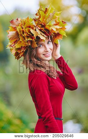 Beautiful Young Woman Smiling With A Wreath Of Leaves On Her Head. Outdoor Portrait In Autumn Park