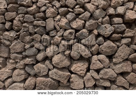 Background -  wall made of pieces of volcanic lava, gray and brown