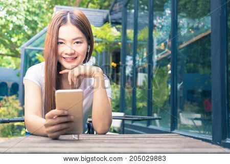 young happy asian woman looking smiling at camera wearing earphone and holding her phone at an outdoor cafe with blurred background trees duo tone colors warm high light and cool blue shadow good for communication technology or relationship concept