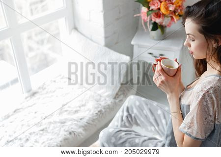 Sensual young woman with cup of tea at home. Every morning ritual for good start of the day. Thoughtfulness and calmness, relaxation and perception concept