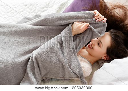 Smiling woman tries to wake up in the morning. Past dreams, calmness and relaxation, staying in bed for a while close up picture