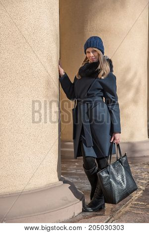 Young beautiful blonde girl in blue coat with fur in a knitted cap with a black big bag walks through the winter and spring city