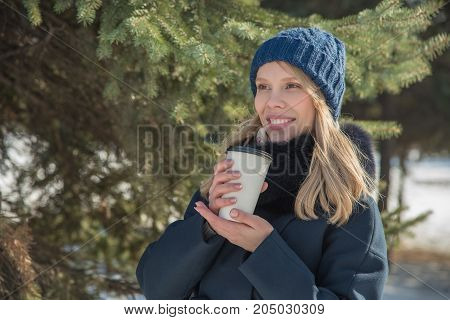 Beautiful girl walking in winter city park with a black bag and drink delicious hot coffee
