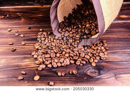 Roasted Coffee Beans In Sack On Wooden Table