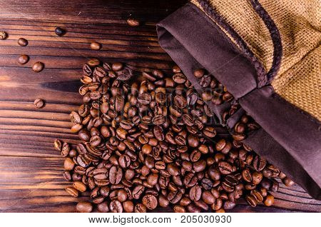 Roasted Coffee Beans In Sack On Wooden Table. Top View
