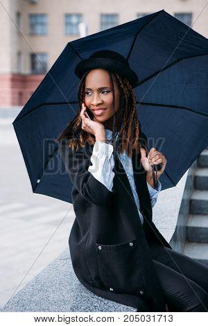 Happy conversation. Modern social communication. Moody weather. Joyful black female with an umbrella on rainy day, street fashion, happiness concept
